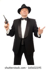 The elegant man in a tuxedo with a hat and a revolver on a white background.