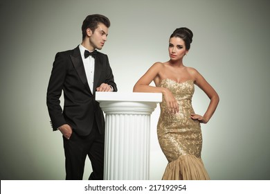 elegant man in tuxedo looking at her sexy woman posing in studio