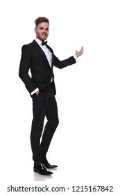 elegant man in tuxedo presenting something on white background