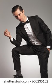 elegant man in tuxedo snapping finger and looks at the camera on grey background