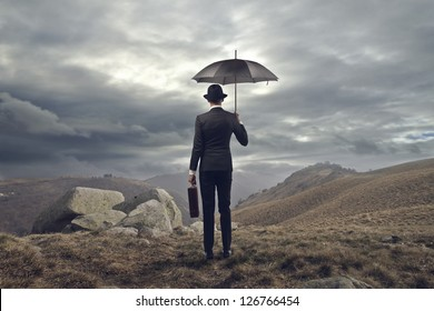 elegant man with umbrella shot from behind in the mountains