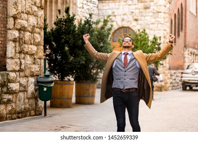 An elegant man walking on the streets and cheering.
