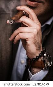 elegant man wearing suit and white shirt smoking  cigar indoor shot, closeup, selective focus