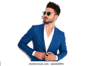 elegant man wearing sunglasses buttoning his suit and looks away to side on white background