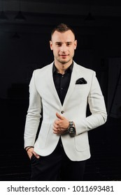 elegant man in a white suit with bristles and a handkerchief. studio ptrait on a dark background of beautiful and sexy guy.Party man ready.