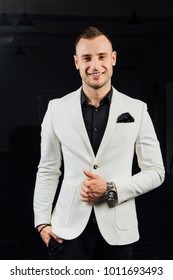 elegant man in a white suit with bristles and a handkerchief. studio ptrait on a dark background of beautiful and sexy guy.Party man ready. laughs.