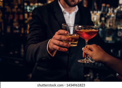 Elegant man and woman are consuming alcohol at the posh restauraunt together.