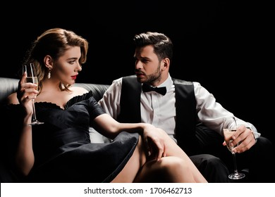 elegant man and woman sitting on leather sofa with glasses of champagne and looking at each other isolated on black