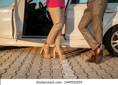 Elegant man and woman (unrecognizable) standing by modern car, flirting