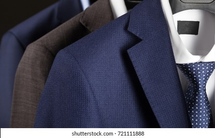Elegant man's suits hanging in a row - closeup shot of classical man't suites