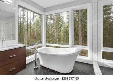 Elegant Master Bathroom Interior in New Luxury Home, Featuring Bathtub, Sink, Tile Floor, and Beautiful View of Trees and Forest.