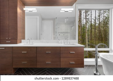 Elegant Master Bathroom Interior in New Luxury Home, Featuring Bathtub, Sink, Tile Floor, and Beautiful View of Trees and Forest. Shower is Shown in Mirror Reflection.