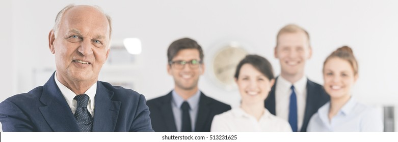 Elegant, mature businessman standing with the smiled work team at the background