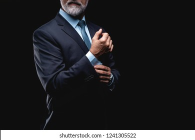 elegant mature fashion man looking at his cufflinks while fixing them