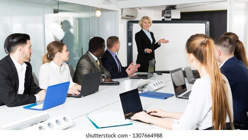 Elegant mature female chief gathering her managers for conference in modern meeting room