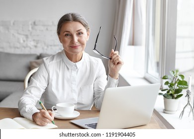 Elegant mature female psychologist working in modern office, holding eyeglasses and writing down in her diary, sitting at dews, using portable computer, smiling confidently, enjoying her work