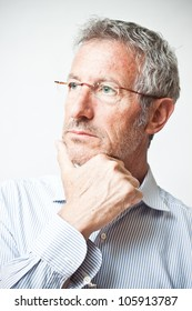 Elegant mature man portrait wearing a pair of glasses lost in thought