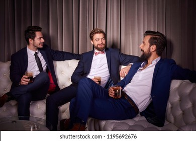 Elegant men with whiskey at night club