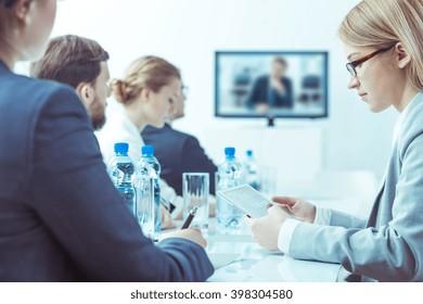 Elegant men and women sitting in light office, having video conference