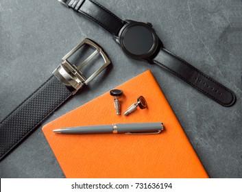 Elegant men`s business accessories. Black watches, belt, notepad, pen, cufflinks.