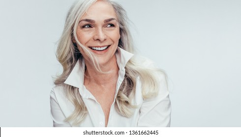 Elegant mid adult woman against white background. Stylish mature woman in white casuals looking away and smiling.