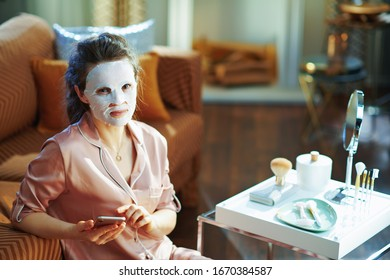 elegant middle age woman in pajamas with white sheet facial mask on face watching video in internet via smartphone at modern home in sunny winter day.