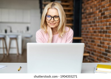 Elegant middle-aged businesswoman wearing stylish glasses using with a laptop indoor. Charming blonde woman working the loft style office
