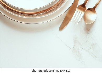 Elegant minimalist gold and white table setting against open white marble table with room for copy.
