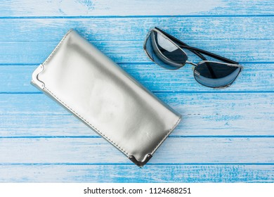Elegant Modenr Woman Reflective Material Purse With Fashion Sunglasses Next To It On Blue And White Wood Background Top Angle