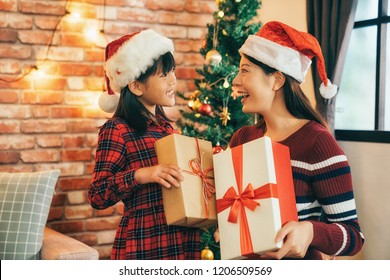 elegant mom sending gift to cute girl in living room. two girl wearing santa hat in xmas eve. celebrate christmas at home concept. present from online shopping on boxing day.