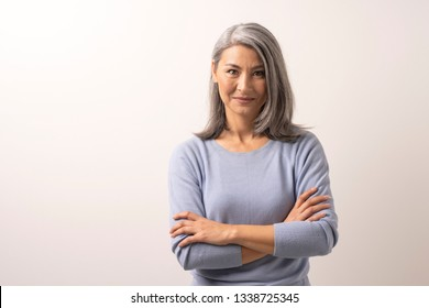 Elegant Mongolian Woman with Gray Hair. Arms Crossed She Smiles Sweetly. Mongolian Beauty Concept. Close Up Shoot.