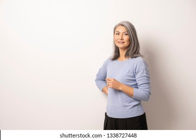 Elegant Mongolian Woman on a White Background. She Smiles Sweetly. Woman is Wearing a Blue Sweater and Black Pants. Mongolian Beauty Concept. Close Up Shoot.