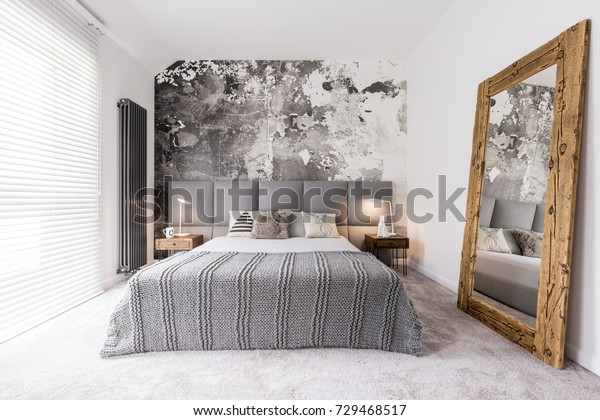 Elegant, monochromatic bedroom reflected in a wood framed mirror supported by the wall