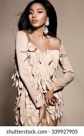 Elegant mulatto girl on beige background