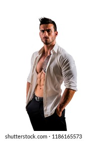 Elegant muscular attractive young man with white shirt open on naked torso, isolated against white wall