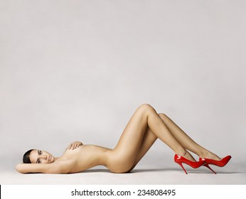 elegant naked woman in red shoes laying on white background