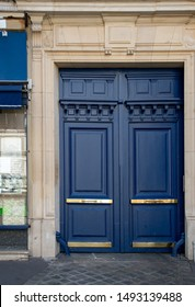 Elegant navy blue painted antique framed door of old building in Paris France. Matte painted wooden door panels and glossy shiny golden metal plates on its. Vintage doorway of ancient stone house