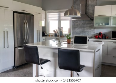 elegant new modern home kitchen with island counter with a computer laptop on it