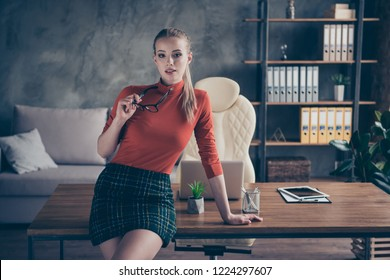 Elegant nice-looking good-dressed lady she stand near table inside loft interior in her red style stylish trendy turtleneck look at camera with calm face