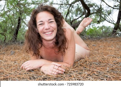 Elegant nude woman laying on the sand natural beach