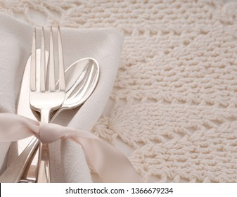 Elegant off white table place setting with silverware of fork, spoon and knife on cream cloth napkin and table cloth with room or space for copy, text, your words.  Horizontal top view