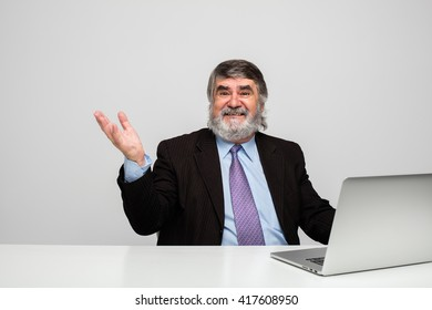 elegant old men using a laptop on a white table