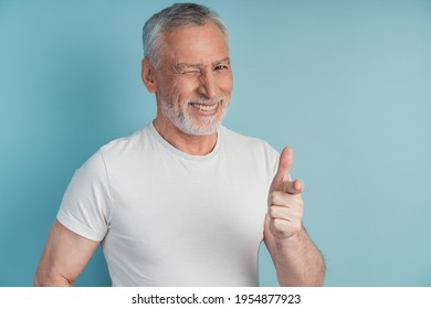 An elegant, older man winks and points with his index finger. Man on a blue background, copy space