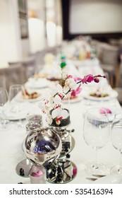 Elegant orchid stands in vase on white dinner table