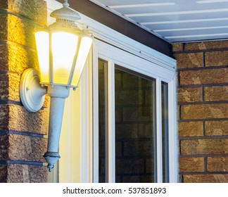 Elegant ornate porch light glowing by front door, welcoming inviting scene