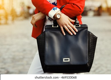 Elegant outfit. Close up of black leather bag handbag in hands of stylish business woman. Fashionable girl on the street. Sunny day. Female fashion concept.  City lifestyle