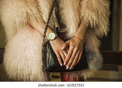 Elegant outfit. Close up of black quilted leather bag handbag in hands of stylish woman. Fashionable girl. Female fashion concept. City lifestyle. fur coat. no face