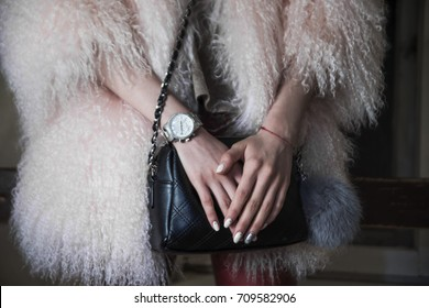 Elegant outfit. Close up of black quilted leather bag handbag in hands of stylish woman. Fashionable girl. Female fashion concept. City modern lifestyle. fur coat. no face. black suitcase