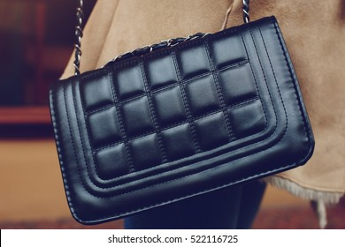 Elegant outfit. Close up of leather quilted black bag. Fashionable girl on the street. Female fashion. City lifestyle. Toned