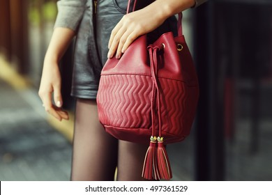 Elegant outfit. Closeup of red leather bag in hands of stylish woman. Fashionable girl on the street. Female fashion. City lifestyle. Toned